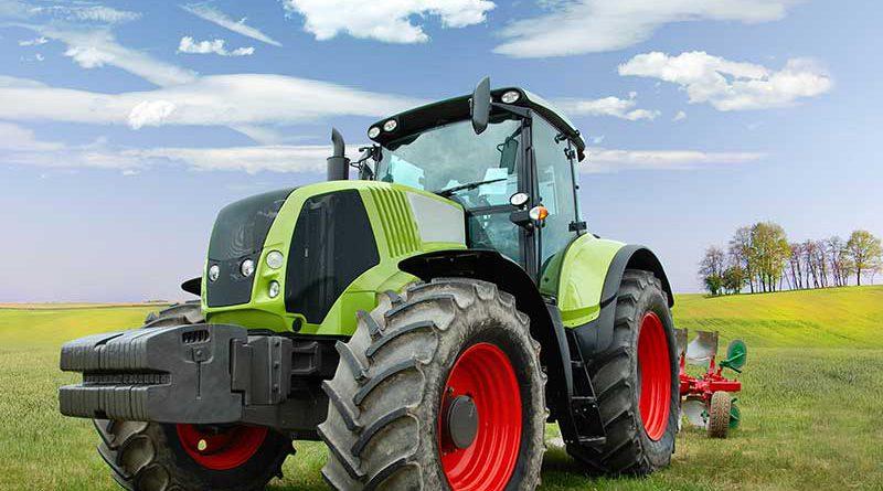 Traktor auf Feld mit Pfluggerät.