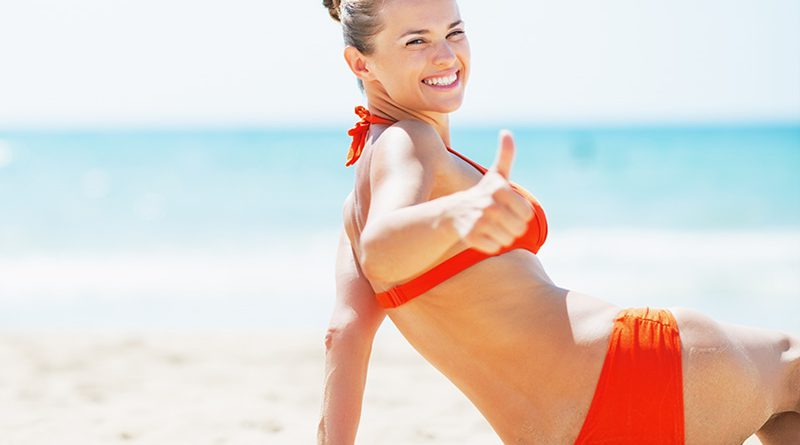 Frau mit rotem Bikini am Strand.